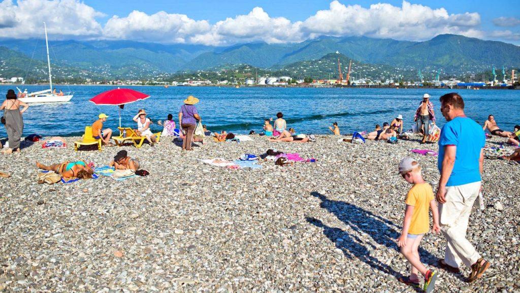 Отдыхающие пляжа со своими полотенцами, городской пляж, Батуми, Грузия